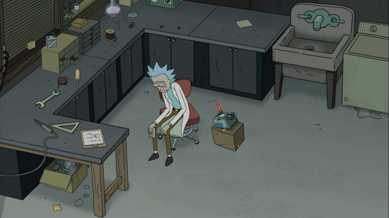 A devastated Rick hangs his head in sorrow in the middle of his garage lab.