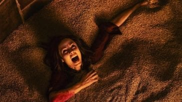 Bloody woman screams as she sinks into a sand pit.