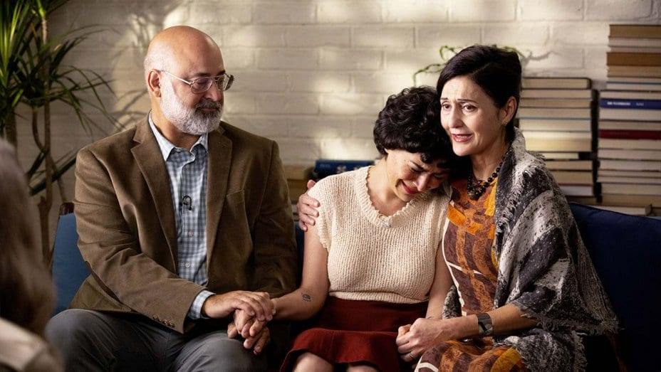 Dory (Alia Shawkat) cries on her mother's shoulder as her father comforts her on the other side.