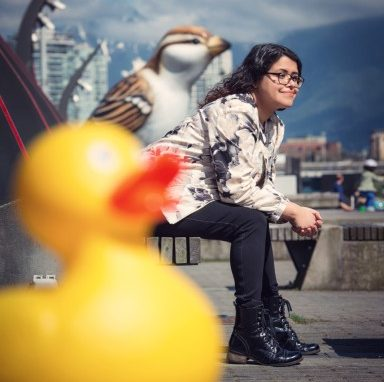 Photograph of smiling author sitting in a park with plastic birds in foreground and cityscape in background.