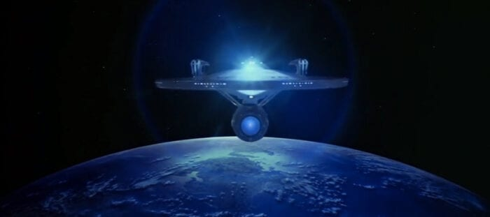 The starship Enterprise flies above Earth
