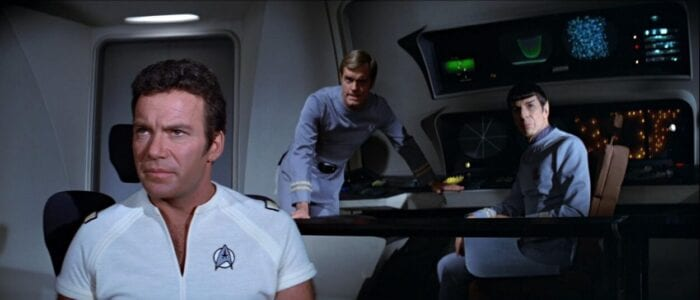 Kirk, a leaning Decker, and a seated Spock look at the viewscreen