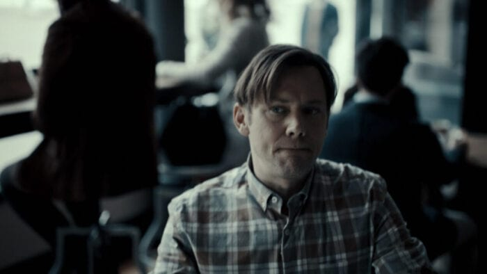 Phil Hayes (Jimmi Simpson) sits at a table hearing voices in his head