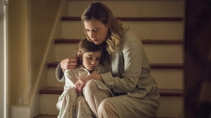 Annie Mitchell (Gillian Jacobs) sits with her daughter on a set of stairs