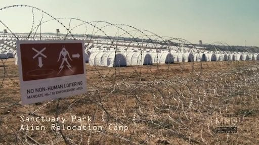 There are many white tents lined up in rows as far as the eye can see, the area is surrounded by barbed