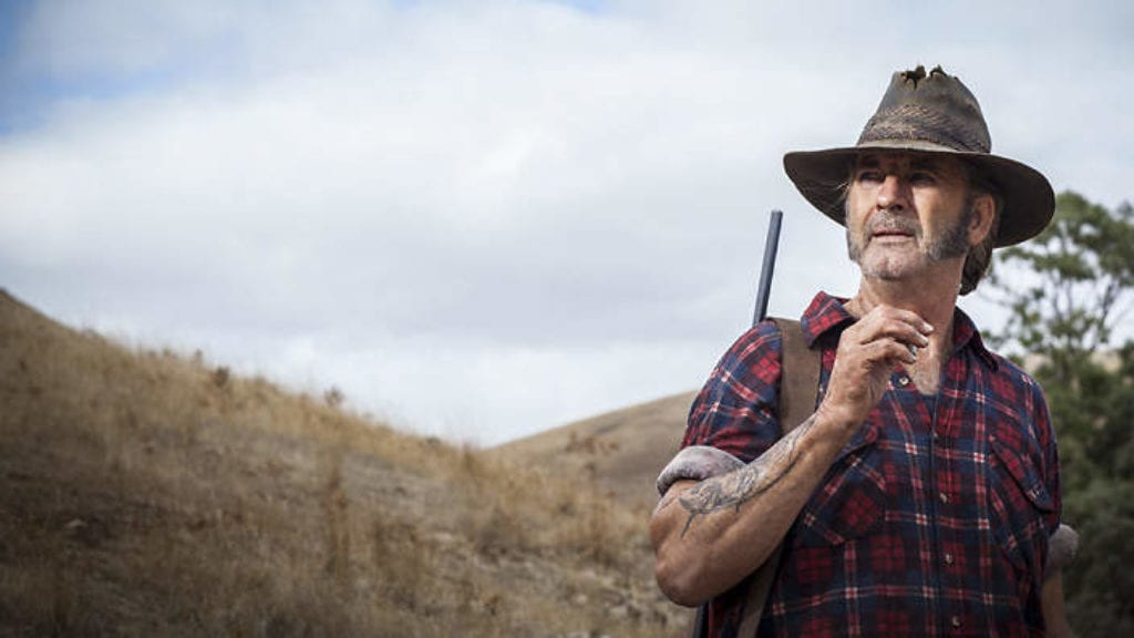 Mick Taylor stands in the wilderness with a rifle slung over his shoulder while he smokes a ciggerate