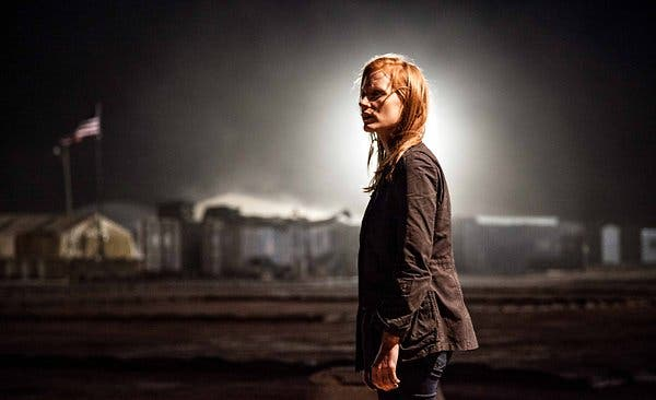 Maya stands in a military airfield at night, flood lights spotlight her