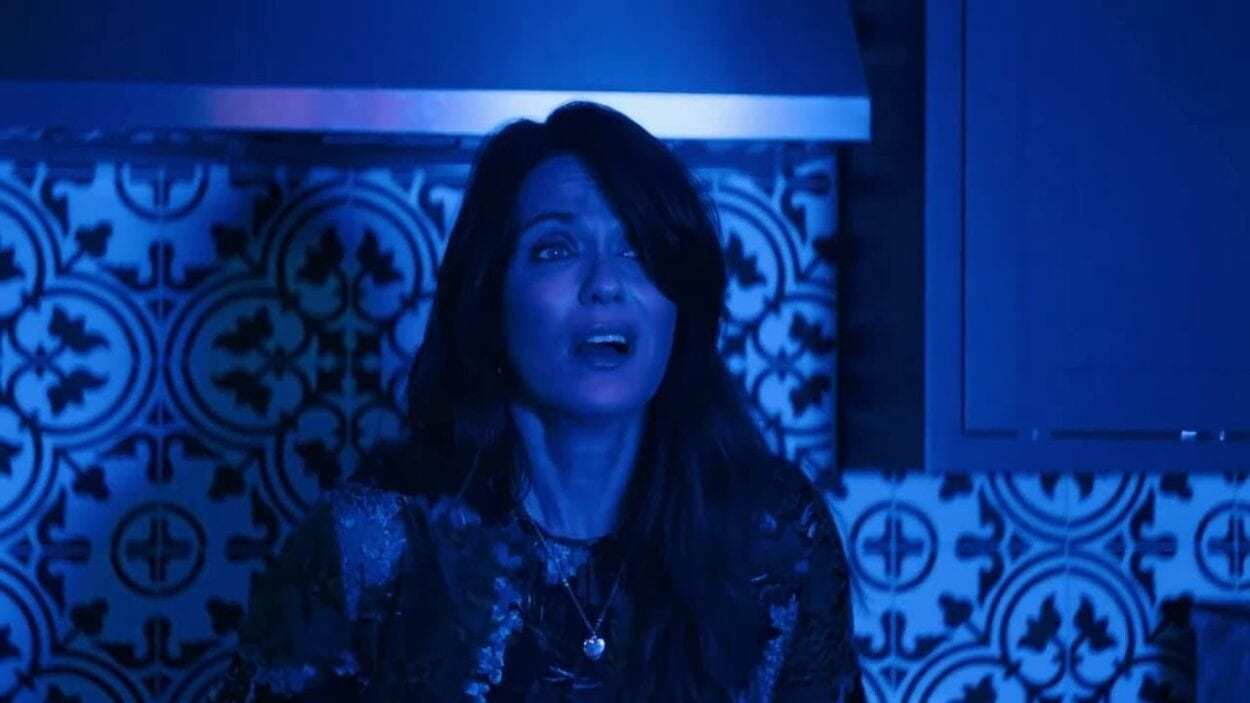 long haired woman facing the camera looking off in the space in front of her bathed in a blue light