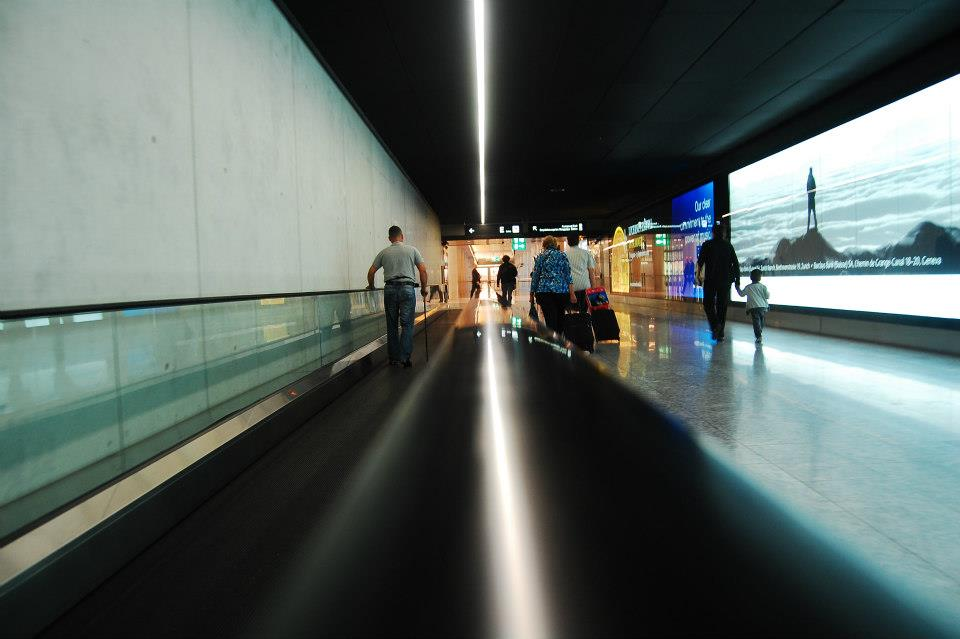 a picture of an airport escalator, with people moving up and down on either sides of the frame.