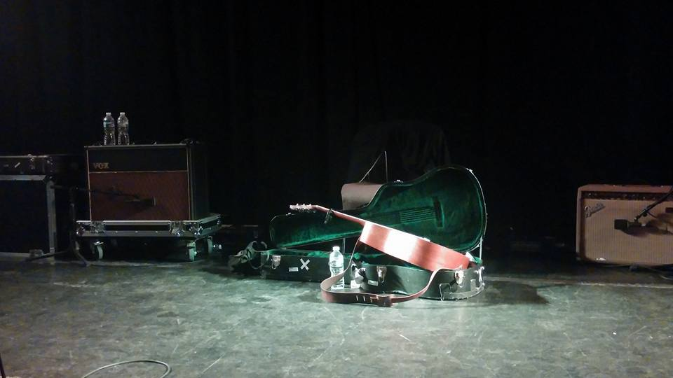 A guitar in its case, on stage and surrounded by amps