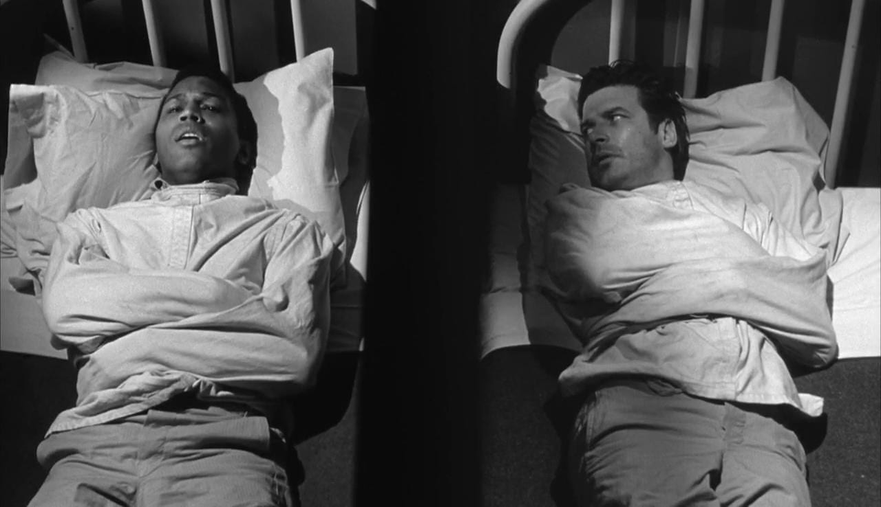 A straitjacketed Trent and Johnny lie in adjacent hospital beds