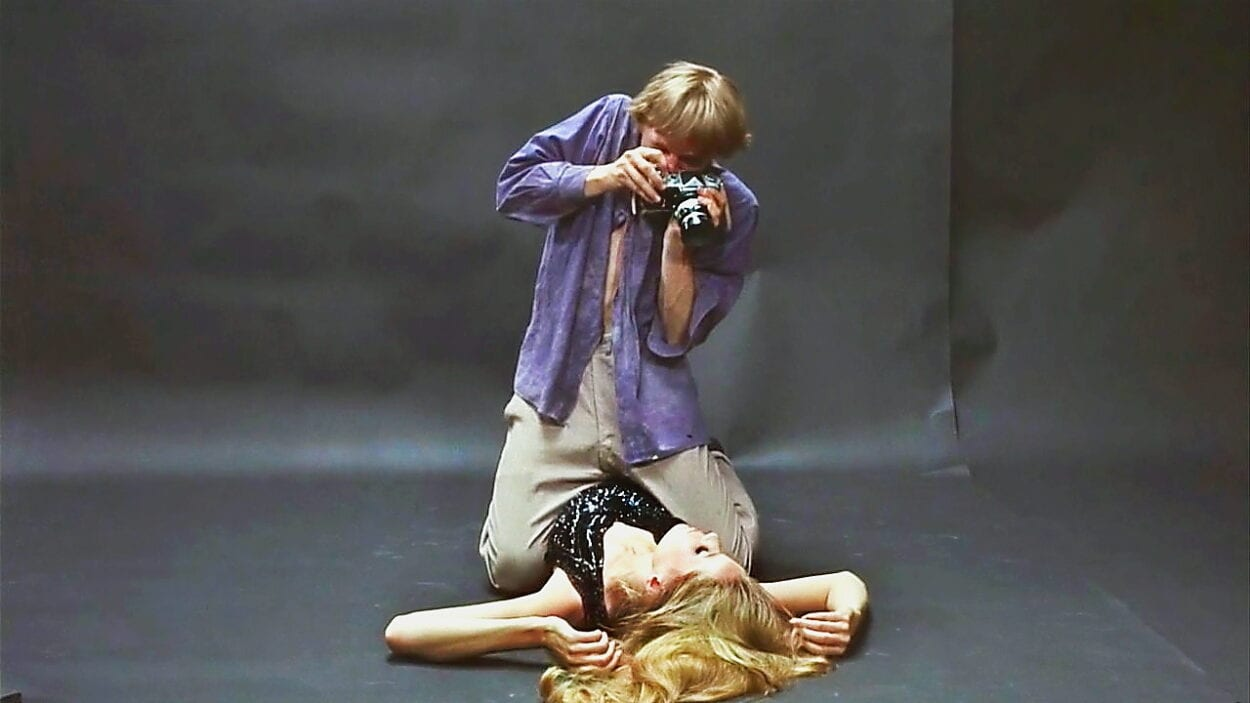 Thomas sits atop model Veruschka in his studio while photographing her