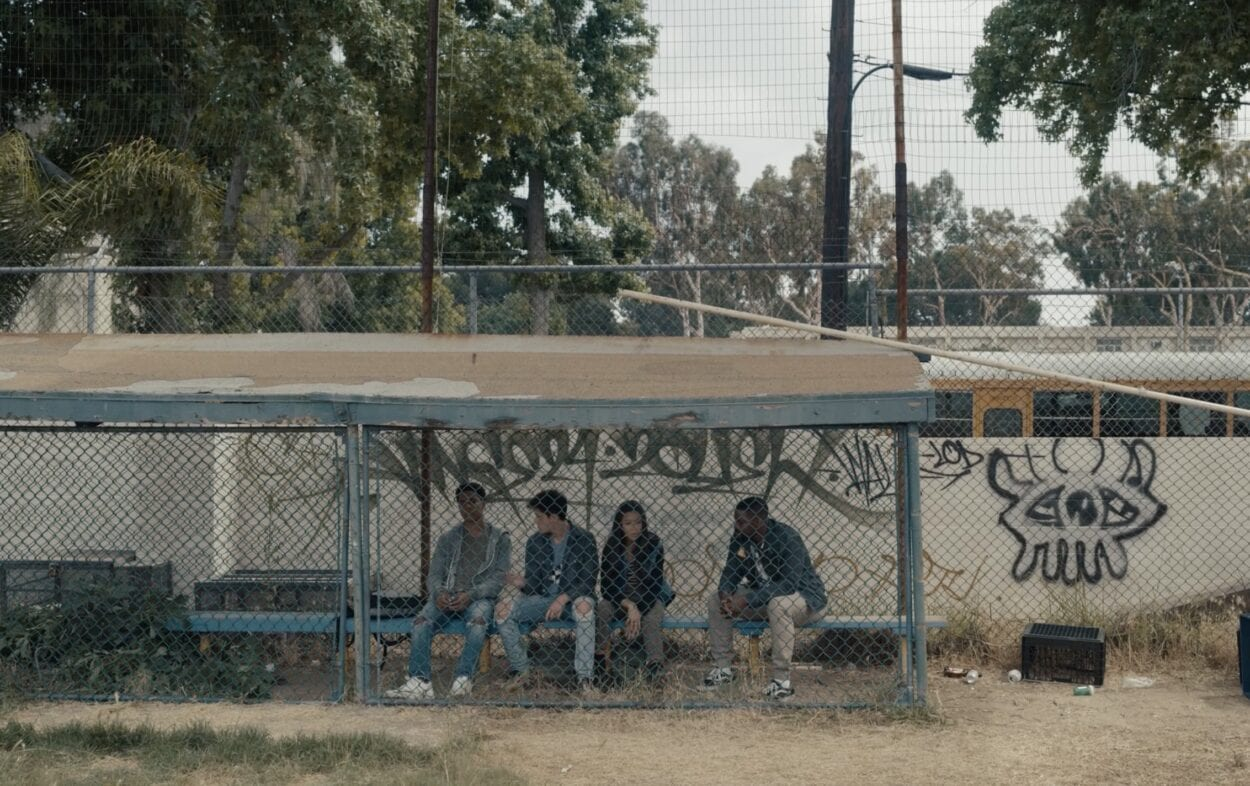 Danny (Jovan Adepo) and three students sit in a dugout while avoiding Matt's remembrance ceremony.