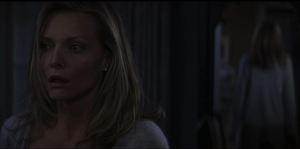 Claire standing, her reflection in a mirror behind her, looking scared as she stares ahead