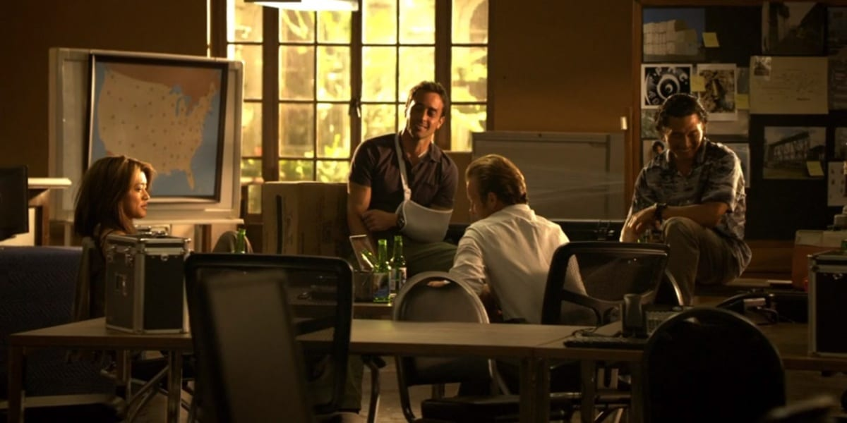 From left to right: Kono, Steve in a sling, Danny with his back to the frame, and Chin, all sitting together in the Pilot laughing and discussing what their team will be called in Hawaii Five-0