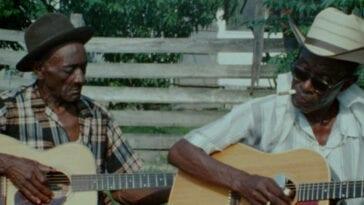 2 older men of colour play acoustic guitar