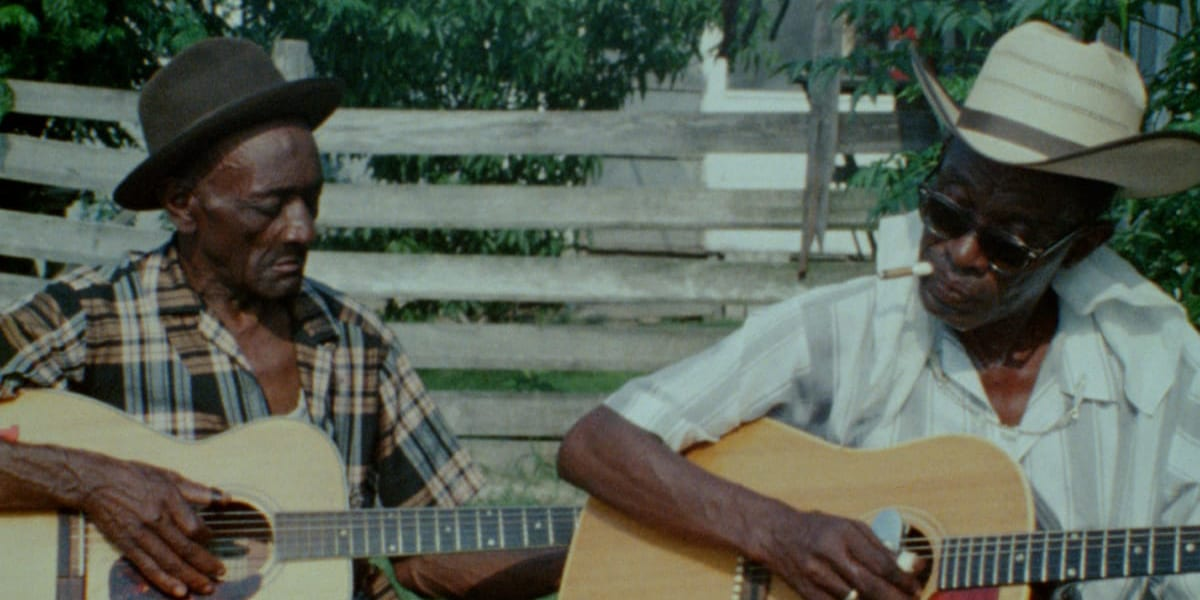 2 older men of colour play acoustic guitar