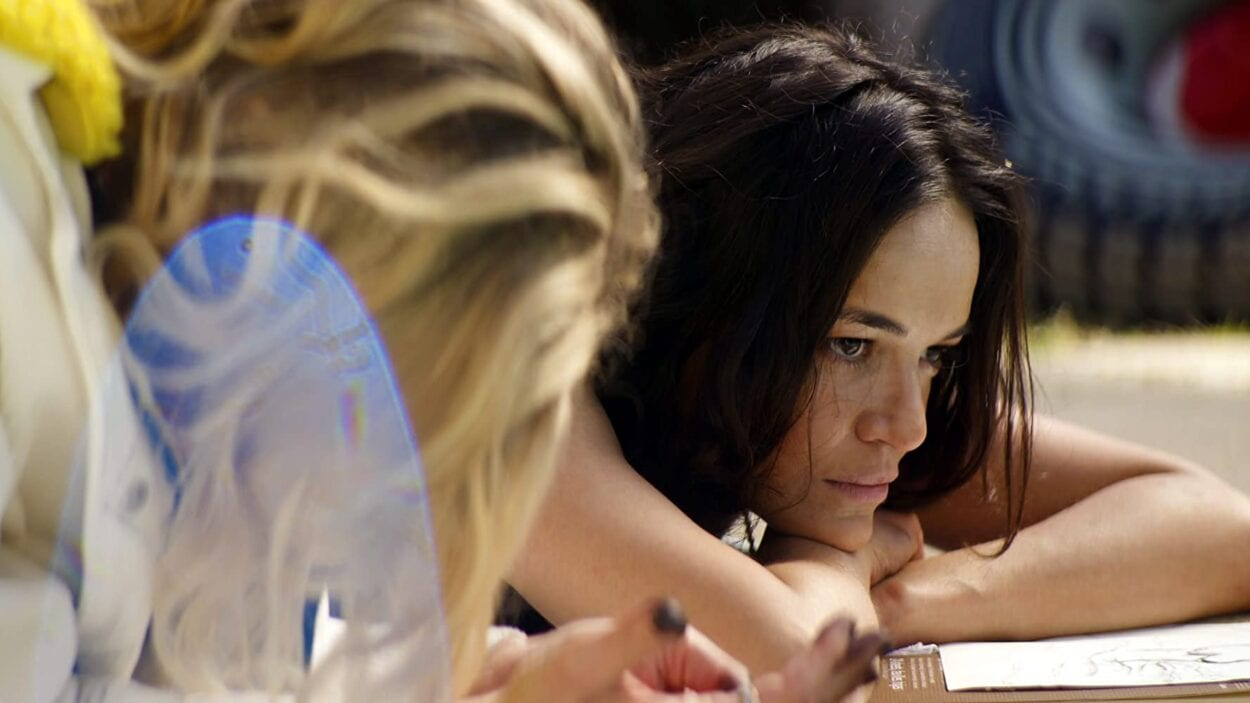 Michelle Rodriguez laying by a pool with a blond woman as they appear in She Dies Tomorrow