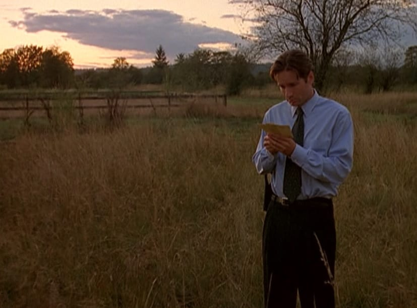 Mulder stands in a field, holding two photographs and looking very forlorn