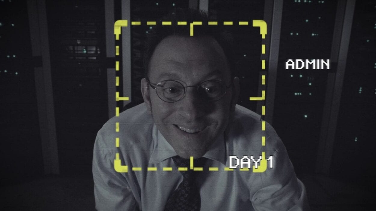 "Harold Finch (Michael Emerson) smiling adorably at the camera, seen from the POV of a webcam with the Machine's UI displaying a yellow square around Finch's face, with text reading ""Admin"" on one side and ""Day 1"" below that"