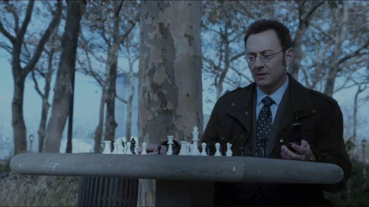 Harold Finch (Michael Emerson) sits at an outside chess table with a cell phone in his hand