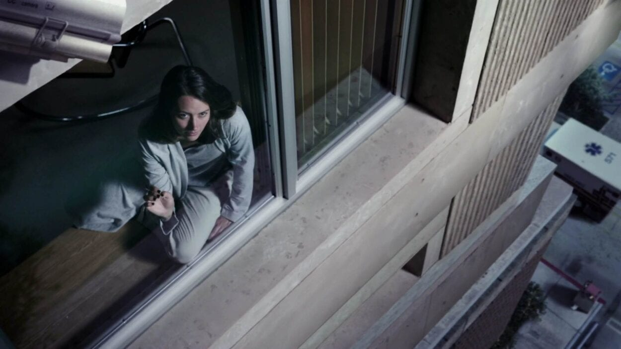 Root (Amy Acker) sitting on the windowsill of a psychiatric hospital, looking outside