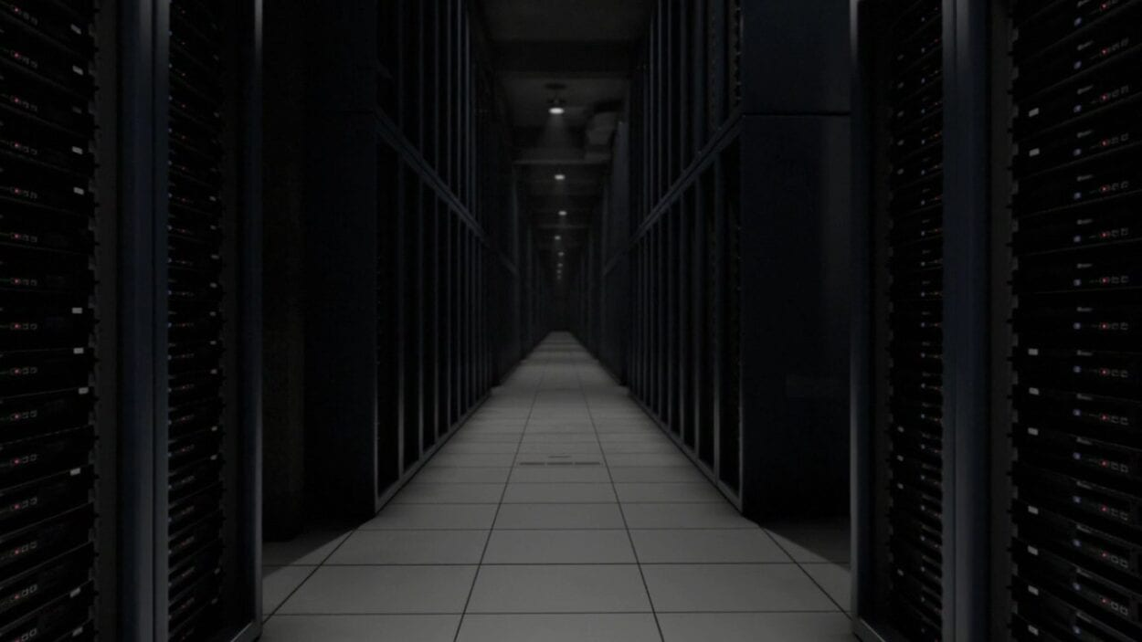 An empty, dimly lit server room filled with rows and rows of computing hardware