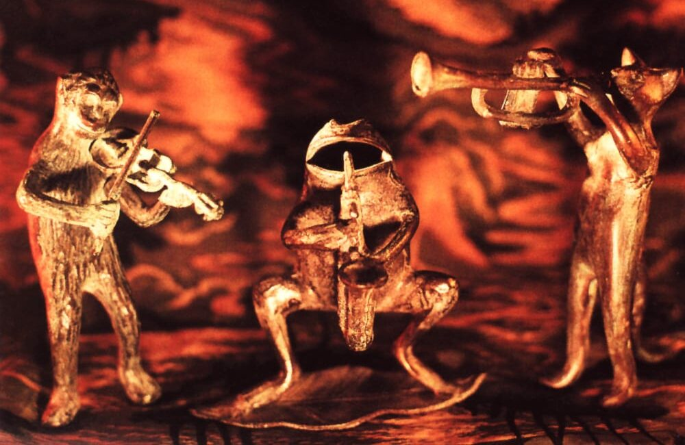 Three gold figurines are as follows: a bear playing fiddle, a toad playing saxophone, and a cat playing trumpet.