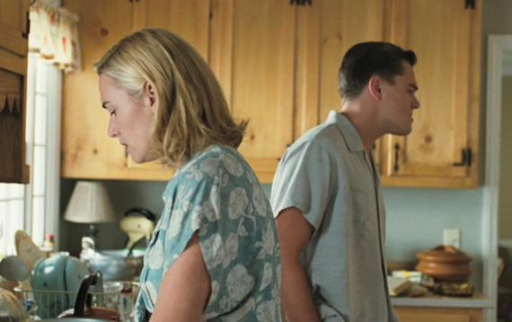 April and Frank Wheeler angry at each other, stood in the kitchen facing away from one another