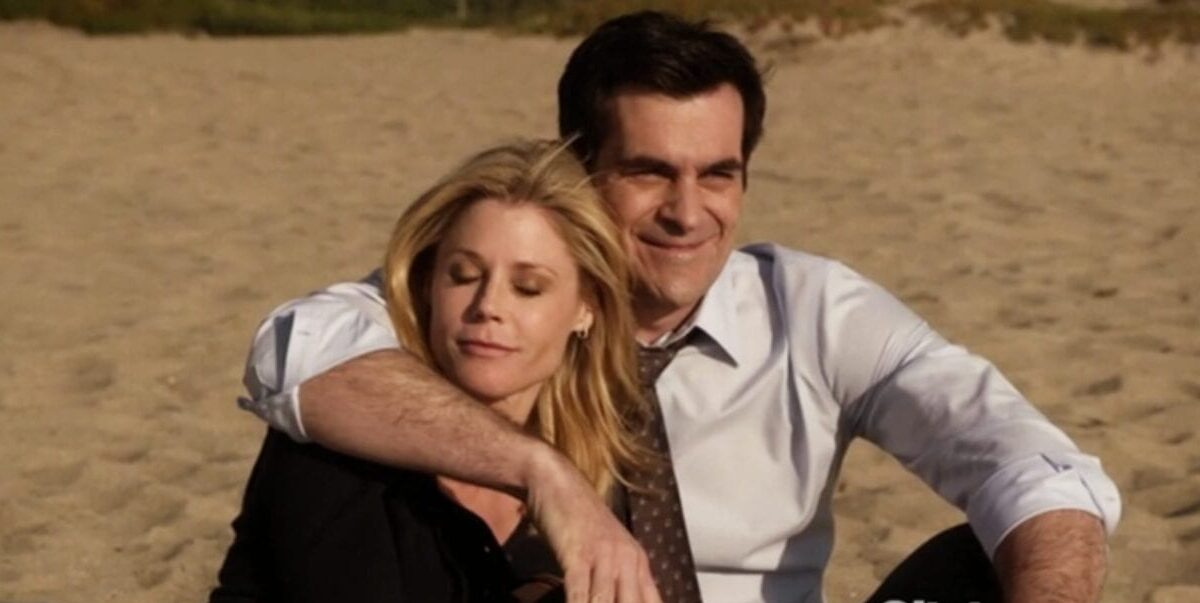 Phil and Claire sit together, cuddling, on the beach