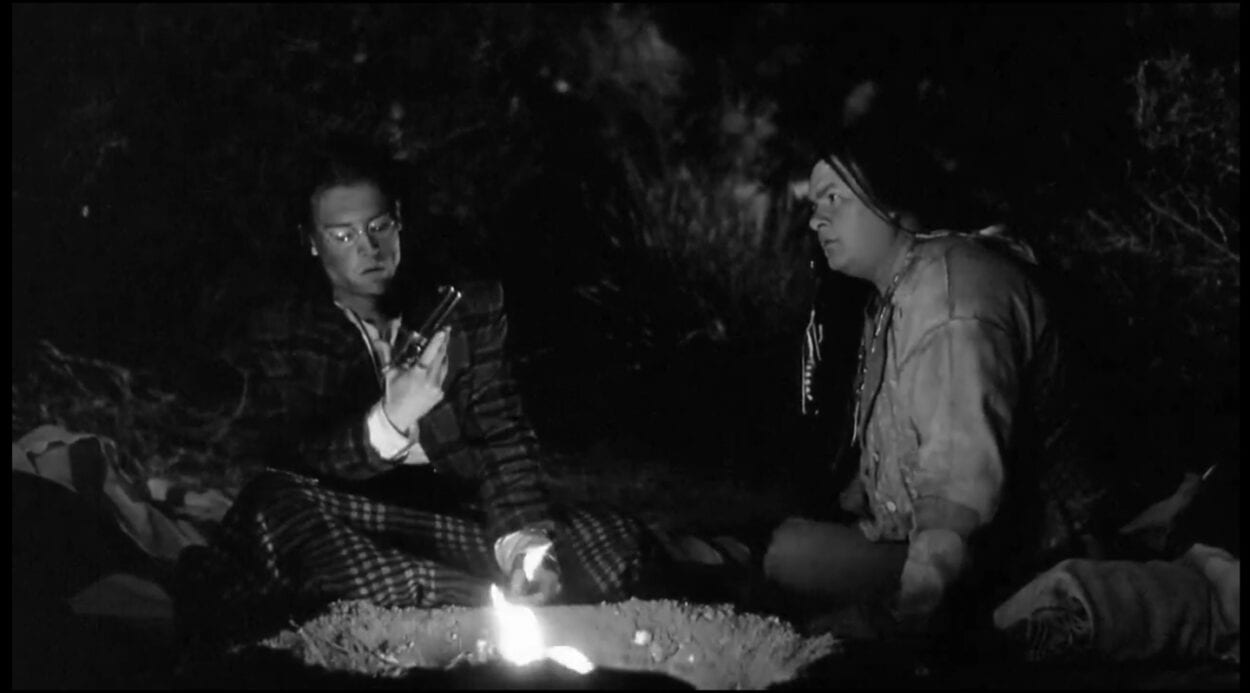 Nobody (Gary Farmer) and William Blake (Johnny Depp) converse with each other at a campfire surrounded by a dark nighttime forest