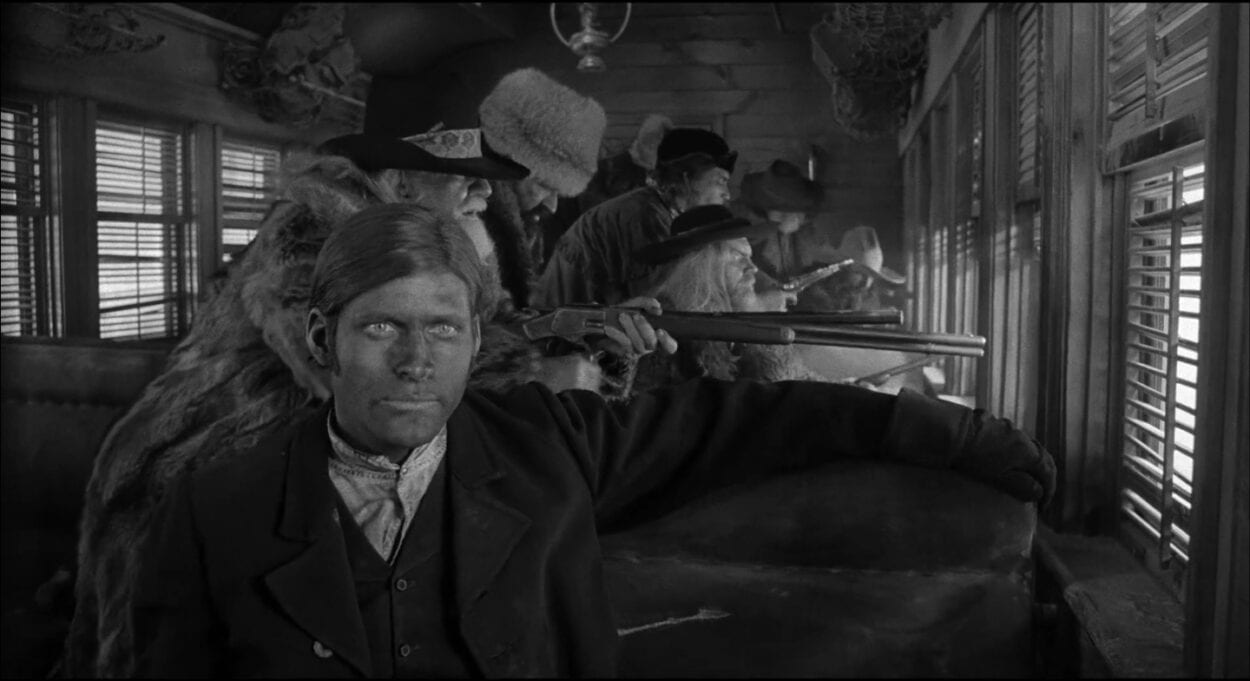 The Train fireman (Crispin Glover) looks just off camera as a group of riflemen shoot their guns out the train window behind him