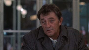 Eddie Coyle (Robert Mitchum) talks with an offscreen Jackie Brown (Steven Keats) at a table