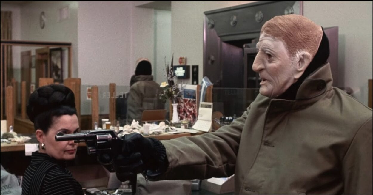 A masked robber aims a handgun at offscreen bank employees while the manager is being escorted away by other masked robbers.