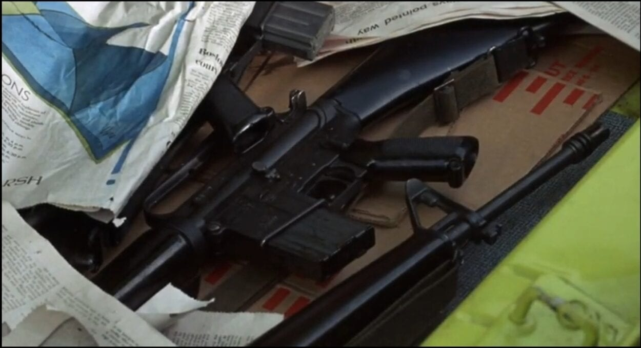 A few assault rifles are hidden underneath newspapers in the trunk of Jackie Brown's (Steven Keats) car