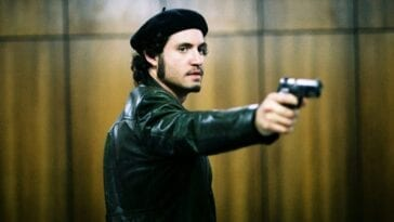Carlos aims a handgun at offscreen hostages during the OPEC meeting