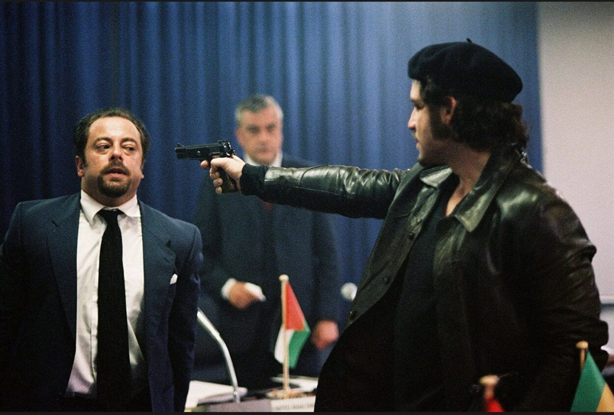 Carlos aims a handgun directly at one of the hostages of the OPEC meeting while another hostage looks on in the background