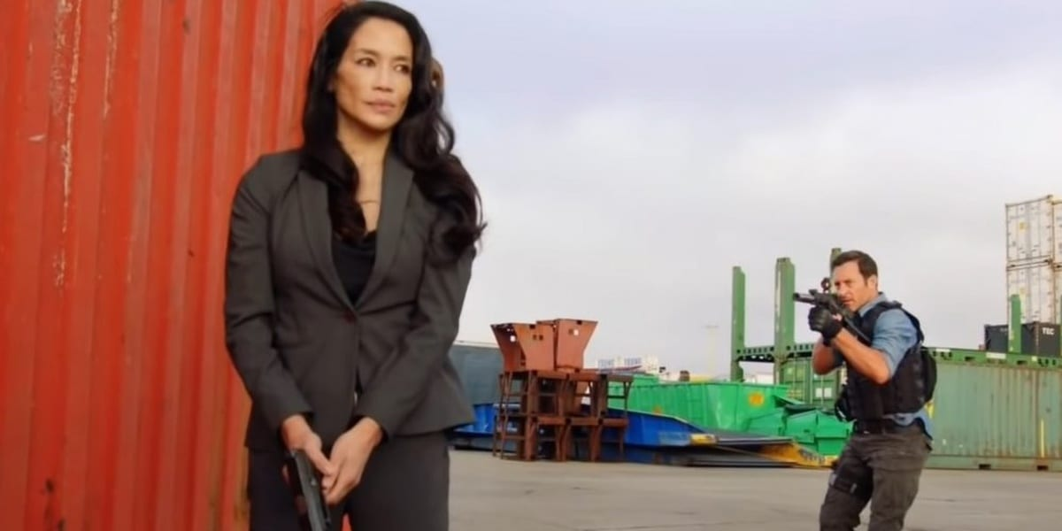 Daiyu Mei standing in front of a shipping container, holding a gun pointing downwards, Steve behind her pointing a gun at her in Hawaii Five-0