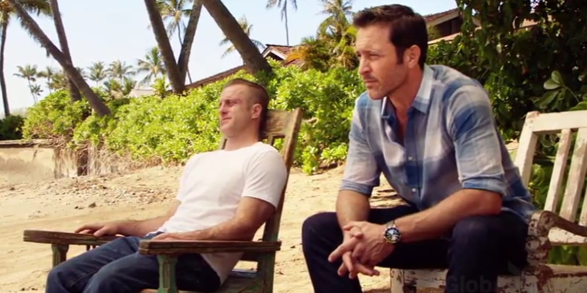 "Steve and Danny in ""Aloha"" sitting on the beach on chairs, Steve sitting with his hands folded and Danny leaning back in his chair, his face beaten up, palm trees in the background"