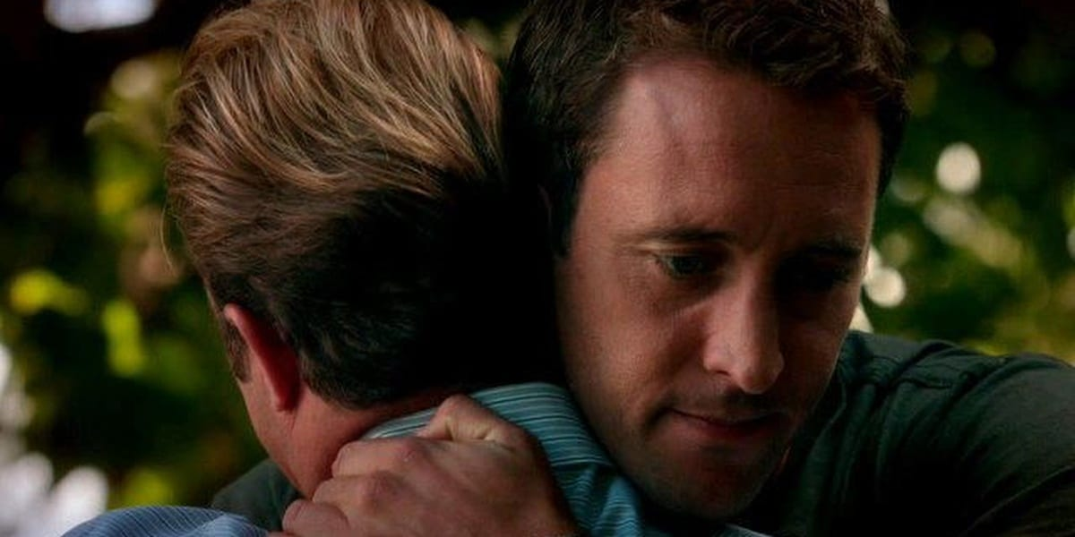 Steve and Danny sharing a hug, the back of Danny's head showing and Steve with a small smile on his face in Hawaii Five-0