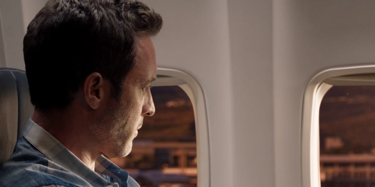Steve quietly looking out the plane's window at Honolulu Airport, some light shining on his face, only the side seen at an angle, in Hawaii Five-0's series finale
