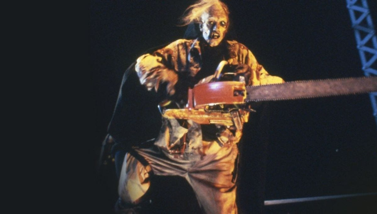 Leatherface stands on a truck, wielding a chainsaw