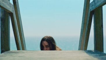 Emily climbs the steps to her beach house after a beach attack