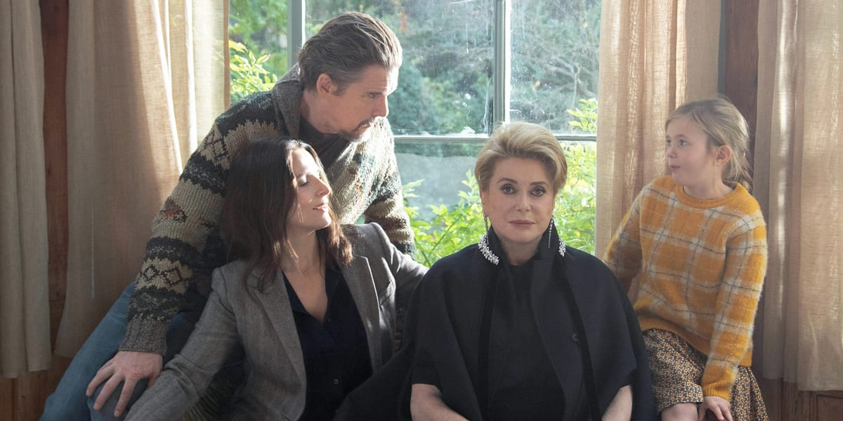 Regal actress Fabienne sits surrounded by her probing family.