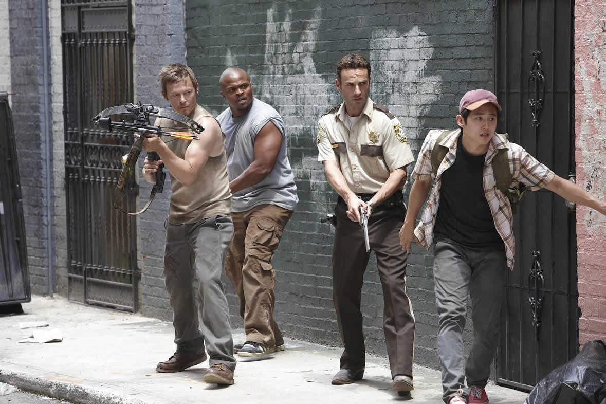 Rick and the gang edge to the corner of a building holding guns
