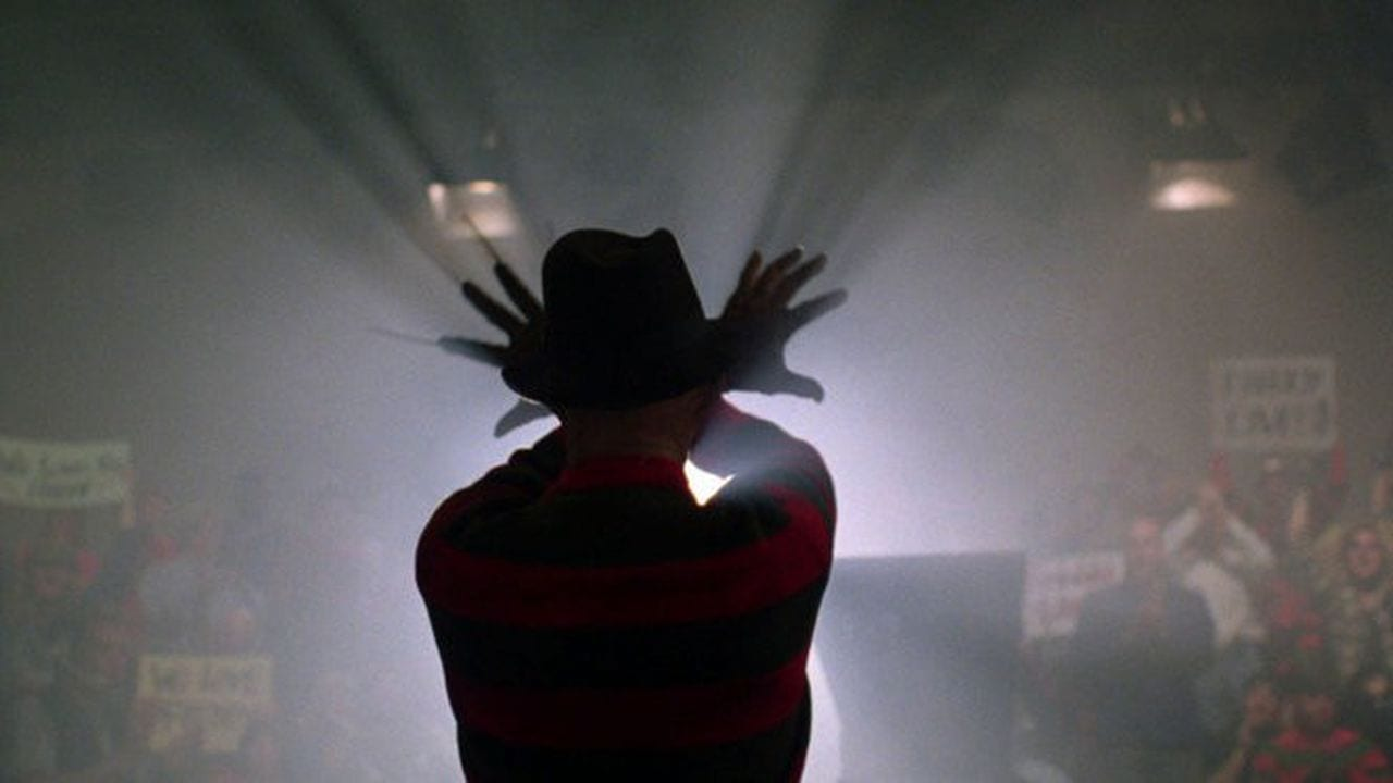 Freddy Krueger wave his arms while a spotlight shines on him