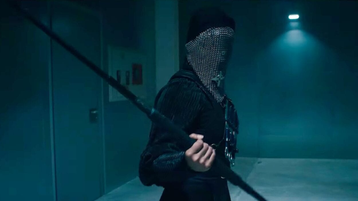 A person with their face fully covered holds a staff in Warrior Nun on Netflix