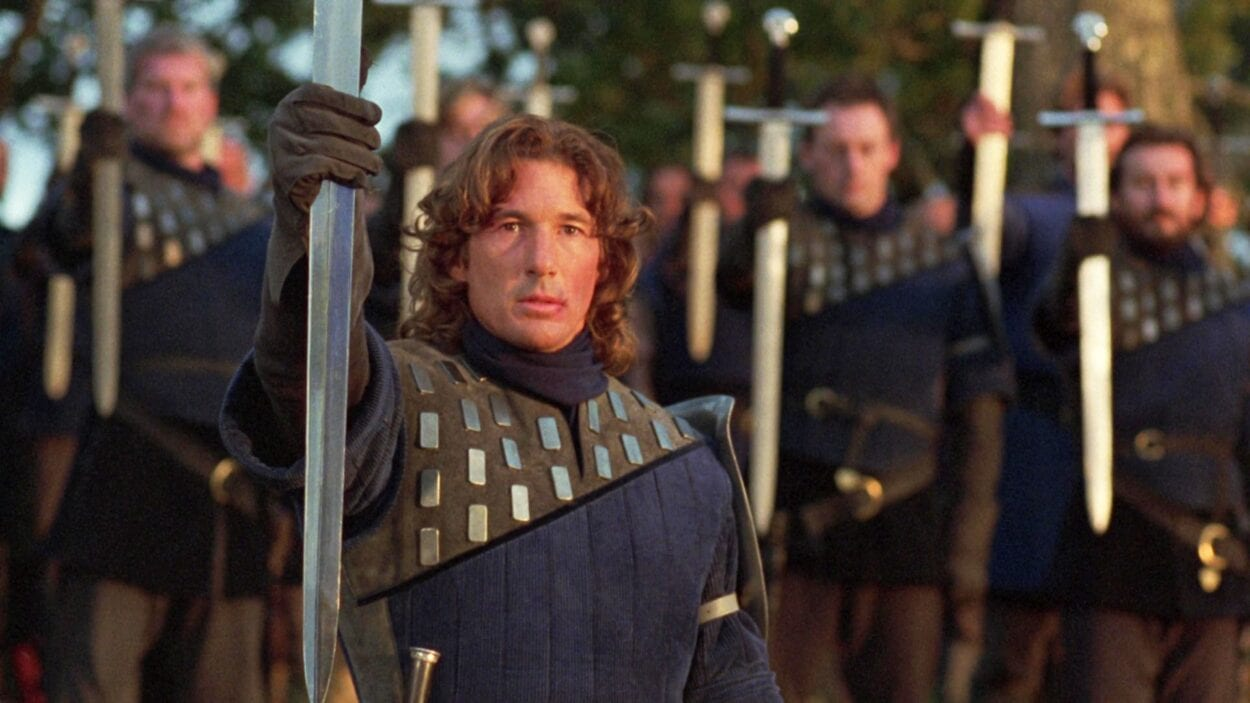 Lancelot holds up a sword in salute at a lakeside funeral.
