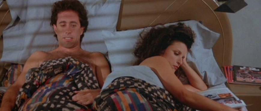 Jerry Seinfeld and Elaine lie in bed, Elaine reads a magazine
