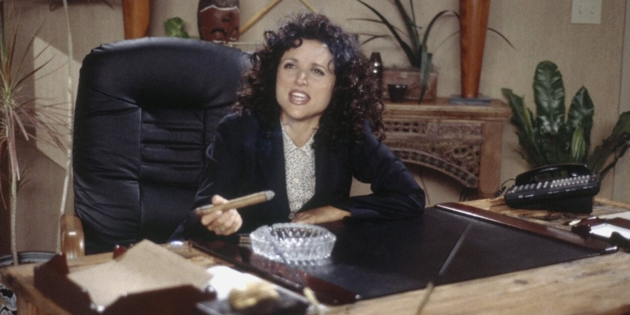 Elaine Benes sits at a desk with a cigar